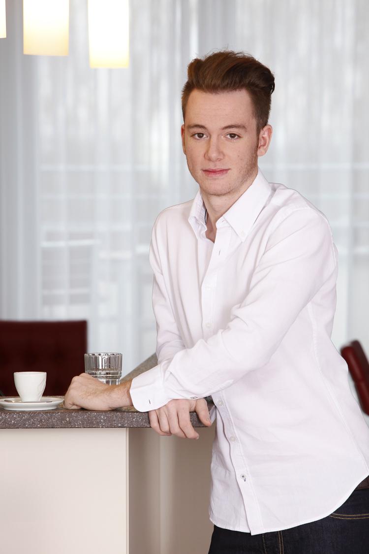Portraitfoto eines jungen Mannes an der Kaffeebar des Fotostudios